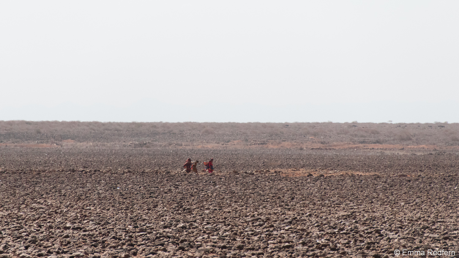 Gabra women walking through a desert of volcanic rock